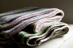 Knitting striped rug with white, green and pink stripes Royalty Free Stock Photo
