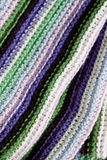 Knitting striped rug with white, purple, green stripes Royalty Free Stock Photography