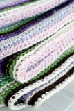 Knitting striped rug with white, purple, green stripes Royalty Free Stock Image