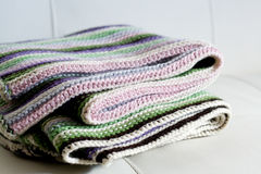 Knitting striped rug with white, purple, green stripes Stock Images