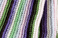 Knitting striped rug with white, purple, green stripes Stock Image