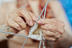 Knitting sweater for son. Senior woman knitting warm sweater for her son with white wool, close-up shot Stock Photography