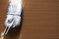 Knitting on the table. Knitting yarn gray  lie on a wooden table with spokes Royalty Free Stock Photo