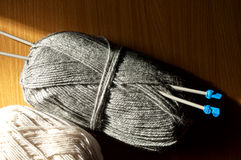 Knitting on the table. Knitting yarn gray and white lie on a wooden table with spokes Stock Photos