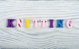 knitting Textura hecha punto de la tela Palabra compuesta de letras del alfabeto de ABC en fondo de madera Foto de archivo libre de regalías