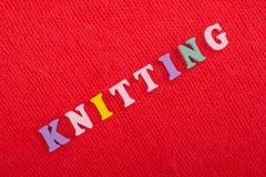 knitting Textura hecha punto de la tela Palabra compuesta de letras del alfabeto de ABC en fondo rojo Fotografía de archivo