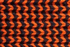 knitting Textura hecha punto fondo Agujas que hacen punto brillantes Hilado de la naranja y de lana negra para hacer punto foto de archivo