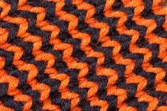 knitting Textura hecha punto fondo Agujas que hacen punto brillantes Hilado de la naranja y de lana negra para hacer punto imagenes de archivo