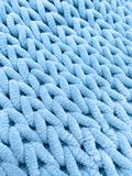 Knitting from thick soft yarn of blue color. Textile background. Stock Image