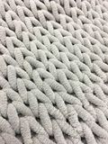 Knitting from thick soft yarn of gray color. Textile background. Stock Image