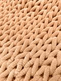 Knitting from thick soft yarn of orange color. Textile background. Royalty Free Stock Image