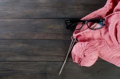 Knitting threads and glasses  on a wooden table. Royalty Free Stock Photography