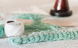 Knitting with threads with strung turquoise beads Royalty Free Stock Image