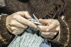 Knitting time. A foreground of two hands knitting a scarf Royalty Free Stock Images