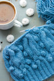 Knitting a turquoise pattern on the circular needles. Knitting a turquoise alpaca wool pattern on the circular needles and a cup of coffee with milk and royalty free stock photography