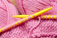 Knitting with Wool. Closeup of knitting with yellow needles and pink wool Royalty Free Stock Images