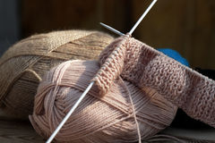 Knitting and wool balls. Started needlework of pink woolen threads on the table Royalty Free Stock Images