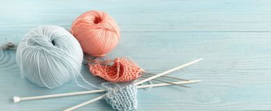 Knitting wool and knitting needles in pastel blue and pink colors. On blue wooden background. top view.copy space royalty free stock photo