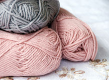 Knitting Wool. Pink and Gray knitting wool on white fabric stock photography