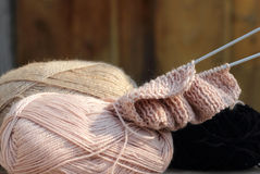 Knitting and wool. Started needlework of pink woolen threads on the table Stock Image