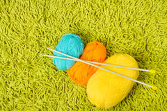 Knitting yarn balls and needles over green carpet Royalty Free Stock Photos