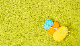 Knitting yarn balls, needles over green carpet background Royalty Free Stock Photos