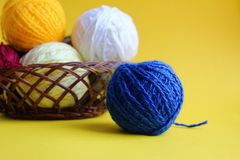 Knitting yarn in different colors on a yellow background royalty free stock image