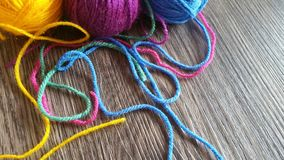 Knitting yarn in rainbow colors. Wool yarn in rainbow colors on a dark wooden background Stock Photos