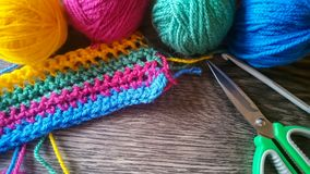 Knitting yarn in rainbow colors. Wool yarn in rainbow colors on a dark wooden background Stock Images