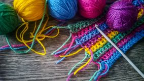 Knitting yarn in rainbow colors. Wool yarn in vibrant rainbow colors on dark wooden background Stock Image
