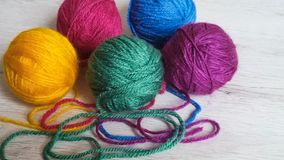 Knitting yarn in rainbow colors. Wool yarn in rainbow colors on a white wooden background Stock Photos