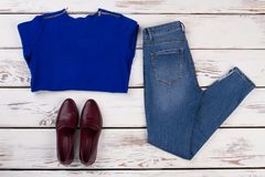 Knitwear blouse, jeans and shoes. Folded clothes on rustic table. Combination of cobalt blue and dark red Stock Photos