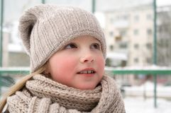 Close up of smiling cute girl with winter knitted hat. Outdoor shot with unfocused blurred background royalty free stock image