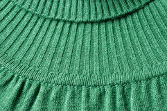 Knitwear detail of green turtleneck jersey. Close up and detail of green turtelneck pullover, knitting pattern and stiches Stock Photo