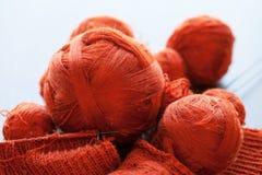 Knitwork anaranjado con las bolas del hilo en una cesta Fotos de archivo