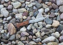 Kniv i bakgrunden av små stenar fotografering för bildbyråer