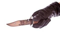 Kniv i den isolerade svarta handsken Royaltyfria Bilder