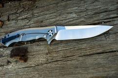 Kniv med ett titanhandtag som fotograferas på en vinkel royaltyfri bild