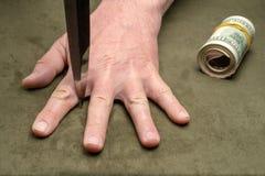 Kniv mellan fingrarna av en mans hand arkivbild
