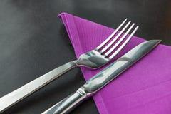 Kniv och gaffel med den violetta servetten Royaltyfri Foto
