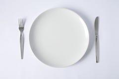 Kniv och gaffel med plattan Fotografering för Bildbyråer