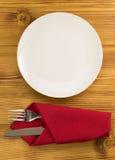 Kniv och gaffel med servetten på trä Royaltyfria Bilder