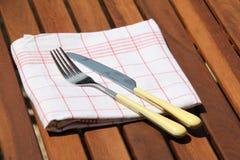 Kniv och gaffel på den kulöra torkduken arkivbild