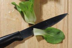 Kniv och grönsallat på att hugga av trä royaltyfria foton