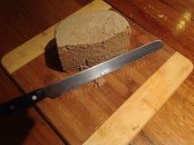 Kniv och hemlagat bröd på lantligt träbräde Fotografering för Bildbyråer