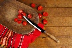 Kniv och körsbärsröda tomater arkivfoto