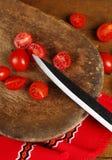 Kniv och körsbärsröda tomater royaltyfria bilder