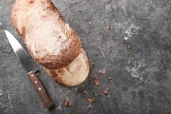 Kniv och nytt smakligt bröd på grå bakgrund royaltyfria foton