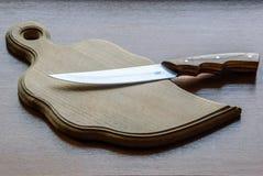 Kniv och träbräde Arkivbild
