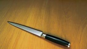 Kniv på brunt träbräde Arkivfoton
